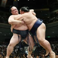 Yokozuna Kisenosato (left) forces out sekiwake Mitakeumi on the 12th day of the Autumn Basho in September at Ryogoku Kokugikan. Kisenosato finished with a 10-5 record and completed a 15-day tournament for the first time since the Spring Basho in March 2017. | KYODO