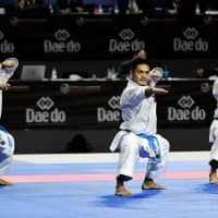 Japan's Ryo Kiyuna (left), Takuya Uemura (center) and Arata Kinjo compete in the male team kata final during the 24th Karate World Championships at the WiZink center in Madrid on Sunday. | AFP-JIJI