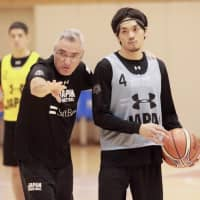 Japan men's national team head coach Julio Lamas instructs his players as guard Ryusei Shinoyama listens during Wednesday's practice in Tokyo. | KAZ NAGATSUKA