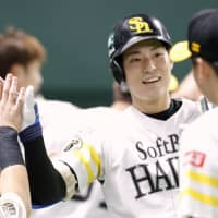 Seiji Uebayashi is congratulated by teammates after homering in the third inning on Wednesday. | KYODO