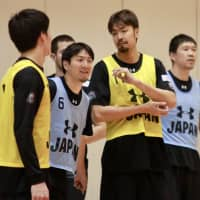 Makoto Hiejima (left) and Kosuke Takeuchi observe the preliminary Japan men's national team's practice on Wednesday. | KAZ NAGATSUKA