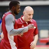 Qatar head coach Panayiotis Yiannaras talks with one of his players during the team's practice in Toyama on Thursday night. | KAZ NAGATSUKA