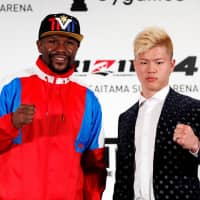 Boxer Floyd Mayweather Jr. poses with his scheduled New Year's Eve opponent Tenshin Nasukawa during a Tuesday news conference to announce his signing with Japanese MMA promoter RIZIN. | REUTERS