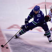 Vancouver's Derrick Pouliot controls the puck against Chicago's Jonathan Toews in the third period at Rogers Arena on Wednesday. | ?ANNE-MARIE SORVIN / USA TODAY / VIA REUTERS