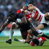 Japanese players converge on England's Maro Itoje during their match on Saturday in London. England won 35-15. | ACTION IMAGES VIA REUTERS