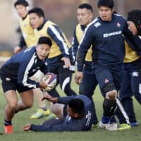 Japan scram half Kaito Shigeno (left) gets in position to pass the ball during the Brave Blossoms' practice on Thursday in Cheltenham, England. | KYODO