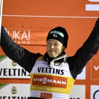 Ryoyu Kobayashi celebrates on the podium after winning a ski jumping World Cup event on Sunday in Ruka, Finland. Kobayashi finished ahead of a pair of Olympic gold medalists to earn the second World Cup title of his career. | REUTERS