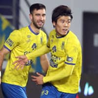 Sint-Truiden's Takehiro Tomiyasu (right) celebrates after scoring against visiting opponents Anderlecht on Sunday. | KYODO