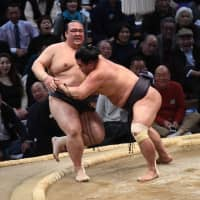Yokozuna Kisenosato (left) is pushed out of the ring by top-ranked maegashira Myogiryu on the second day of the Kyushu Grand Sumo Tournament on Monday at Fukuoka Kokusai Center. Kisenosato fell to 0-2 with the loss. | NIKKAN SPORTS