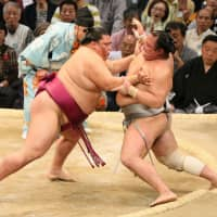 Sekiwake Mitakeumi (left) defeats No. 1 maegashira Hokutofuji at the Kyushu Grand Sumo Tournament on Friday. | NIKKAN SPORTS