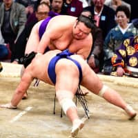 Takakeisho defeats Tochiozan on Wednesday for his 10th win at the Kyushu Grand Sumo Tournament at Fukuoka Kokusai Center. | NIKKAN SPORTS