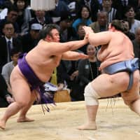 Komusubi Takakeisho (left) shoves No. 12 maegashira Aoiyama en route to victory, improving  to 12-1 at the Kyushu Grand Sumo Tournament on Friday at Fukuoka Kokusai Center. | NIKKAN SPORTS
