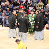 Kisenosato (left) looks on as referees hold a monoii (discussion) to decide the result of his bout against Tochiozan, who was eventually declared the winner. | NIKKAN SPORTS