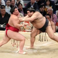 Ozeki Takayasu (right) stays in the Emperor's Cup race by defeating ninth-ranked maegashira Daieisho on Friday. Takayasu is second behind Takakeisho at 11-2. | NIKKAN SPORTS