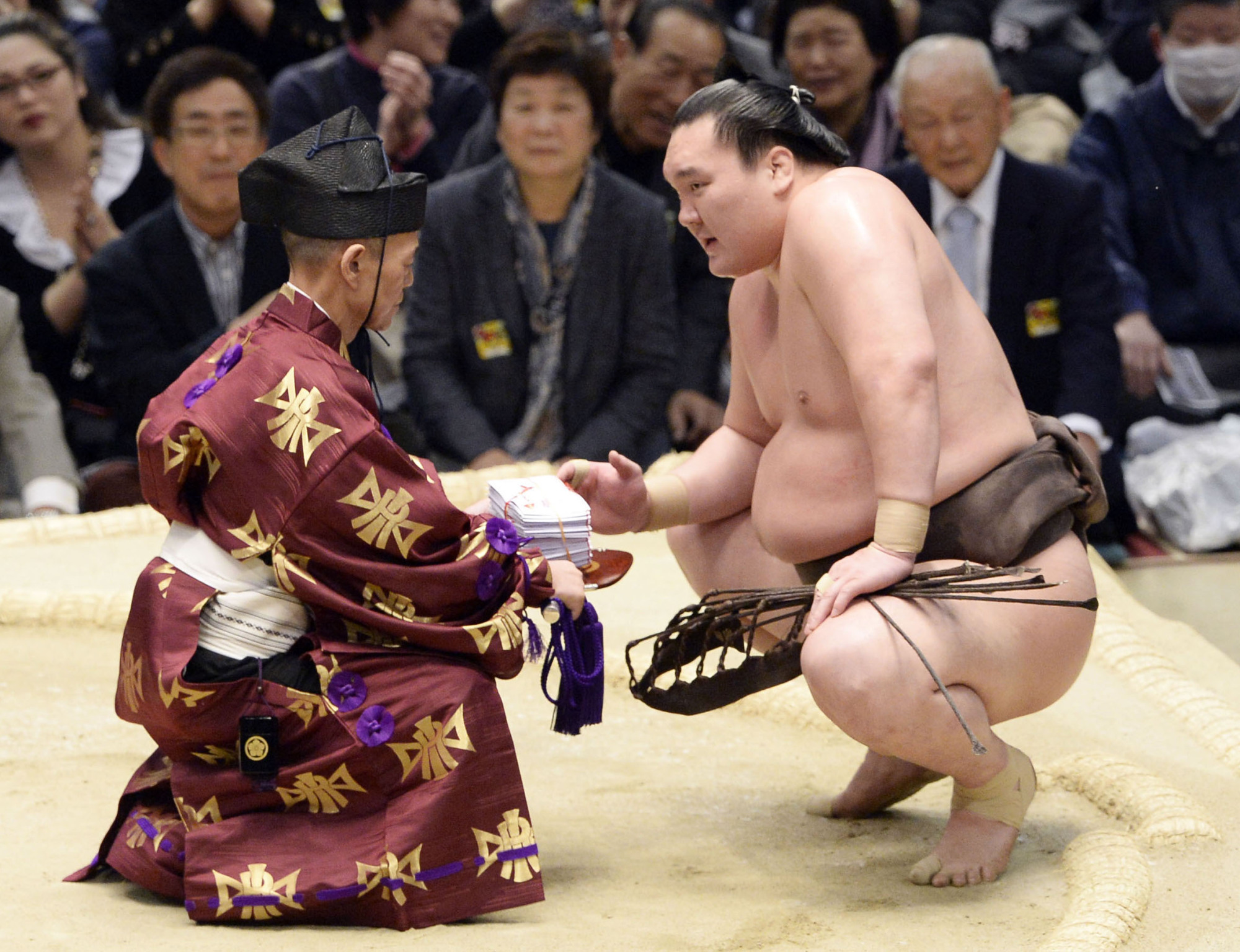 A gyoji gives yokozuna Hakuho his prize money following a victory. | KYODO