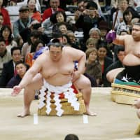 Yokozuna Kisenosato performs a set of movements designed to drive out evil spirits from the ring. | KYODO