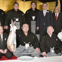 Takakeisho, sitting next to stablemaster Chiganoura (second from right), holds up a sea bream at a celebration of his Kyushu Grand Sumo Tournament championship on Sunday in Fukuoka. | KYODO