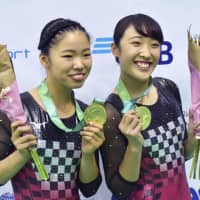 Hikaru Mori (right) and Megu Uyama pose after winning gold at the world championships on Friday. | KYODO