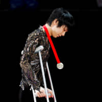 Yuzuru Hanyu walks on crutches after collecting his gold medal at the Cup of Russia in Moscow on Sunday. | REUTERS