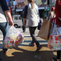 Tourists carry shopping bags in Naha, Okinawa. | BLOOMBERG