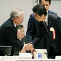 Prime Minister Shinzo Abe, who attended a meeting of Keidanren, shakes hands with Chairman Hiroaki Nakanishi in Tokyo's Chiyoda Ward on Wednesday. | KYODO