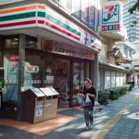 Seven-Eleven Japan Co. has asked its franchise convenience stores in Tokyo to remove all ashtray receptacles set up outside their outlets. | BLOOMBERG