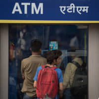 People line up outside an ATM in New Delhi. | GETTY IMAGES / VIA KYODO
