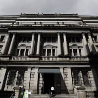 The Bank of Japan will likely wait until after next year's consumption tax hike before taking action to tighten monetary policy, according to a recent Bloomberg survey on economists. | BLOOMBERG