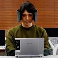 A designer at Panasonic Corp. demonstrates a prototype of Wear Space, wireless headphones designed to reduce surrounding noise and peripheral distractions, in October. | REUTERS