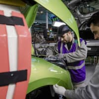 Employees fix fittings to a Nissan Micra automobile inside the Renault SA factory in Flins, France. | BLOOMBERG