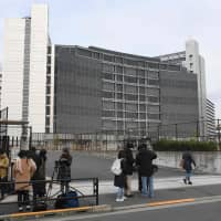 Journalists gather Monday outside the Tokyo Detention House, where former Nissan Chairman Carlos Ghosn is being held. | AFP-JIJI