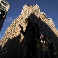 People walk by a building that has been chosen by Google as part of its expansion plans Monday in New York. Google is spending more than $1 billion on a new campus along the Hudson River that will allow it to double the number of people it already employs in the Big Apple.   AP