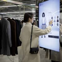 An attendee uses a touch-screen display to try on clothes on a virtual avatar during a media event at the GU Style Studio store in Tokyo on Nov. 29. | BLOOMBERG