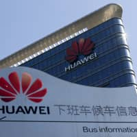 An information board for an employees' shuttle bus is on display near the Huawei office building at its research and development center in Dongguan in south China's Guangdong province Dec. 18. The U.S. dispute with China over a ban on tech giant Huawei is spilling over to Europe, the company's biggest foreign market, where some countries are also starting to shun its network systems over data security concerns. | AP
