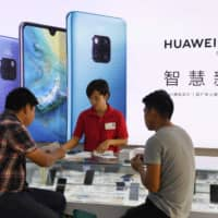 Customers are served at a Huawei stand at a store in southern China's Hainan Island. | AFP-JIJI