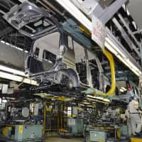 Mitsubishi Motor Corp. employees work on an assembly plant. The nation's industrial output in November fell 1.1 percent from the previous month, government data showed Friday. | KYODO