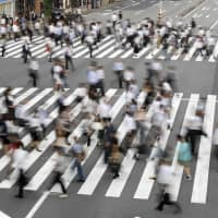 People cross a road near Tamachi Station in Tokyo. The country's unemployment rate climbed for the second consecutive month in November, government data showed Friday. | KYODO