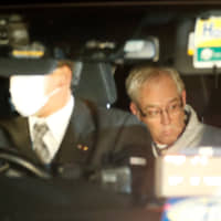Greg Kelly, the former deputy of ousted Nissan Chairman Carlos Ghosn, leaves by car after being released from the Tokyo Detention House on Tuesday. | REUTERS