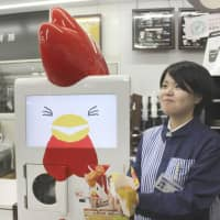 A Lawson employee shows off karaage (fried chicken) prepared by the convenience store chain's new Dekitate Karaage-kun Robo during a trial run that started Tuesday in Shinagawa Ward, Tokyo. | KYODO