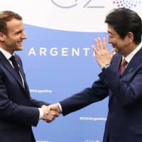 French President Emmanuel Macron shakes hands with Prime Minister Shinzo Abe during a meeting on the sidelines of the Group of 20 summit in Buenos Aires on Friday. | AFP-JIJI