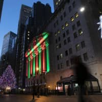 The New York Stock Exchange is bathed in holiday light in New Yor Dec. 11k. U.S. stocks are slightly lower Thursday morning, a day after another big plunge rocked markets around the world. Asian and European indexes suffered bigger losses. Stocks have tumbled as investors grow increasingly worried the U.S. could slip into a recession in the next few years. | AP