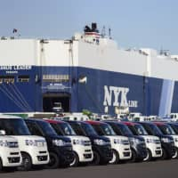 Cars bound for shipment are seen in front of a Nippon Yusen KK car-carrier at a yard in Yokohama. | BLOOMBERG