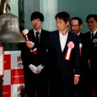 Former national soccer team manager Akira Nishino rings the bell at the Tokyo Stock Exchange on Friday after the bourse ended the year's final trading session. Nishino was invited as a guest to the closing ceremony. | REUTERS