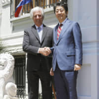 Prime Minister Shinzo Abe is welcomed by Uruguayan President Tabare Vazquez in Montevideo on Sunday. | KYODO