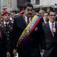 Venezuelan President Nicolas Maduro (center) arrives at the national assembly in Caracas in 2015. Maduro on Monday said to the national assembly that he was recalling Venezuela's ambassador in neighboring Guyana for consultations amid an escalating row over oil exploration in disputed offshore territory. Exxon Mobil Corp. had said it had discovered oil off Guyana's coast, spurring complaints from Caracas that Guyana is unfairly exploiting a disputed territory. | REUTERS