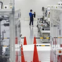 A Yaskawa Electric Corp. employee works on the servomotor assembly line at the company's Solution Factory in Iruma, Saitama Prefecture, in December. Yaskawa Electric manufactures and markets motors, controllers, inverters and industrial robots.   BLOOMBERG