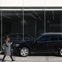 A woman walks past a BMW AG sport utility vehicle parked outside a dealership in Seoul on Monday. BMW is facing a criminal probe in South Korea after investigators concluded the company concealed fire hazards and delayed recalls. | BLOOMBERG