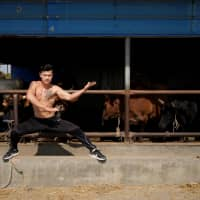 Bullfighter Ren Ruzhi poses at the bull stable of the Haihua Kung Fu School in Jiaxing, China, on Oct. 27. | REUTERS