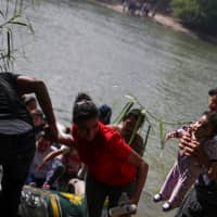 Family units from Central America await their turn on the Mexico side of Rio Grande river as Eliani Valentin, a 5-month-old girl from Honduras, is held by a man after a group used a raft to illegally cross into the U.S. from Mexico in Granjeno, Texas, Oct. 5. | REUTERS