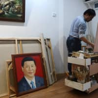 Chen Jingyang works on his original painting as a portrait of the Chinese president Xi Jinping by him is placed on the ground at his studio in Dafen Oil Painting Village in Shenzhen, Guangdong province, China, in December. | REUTERS